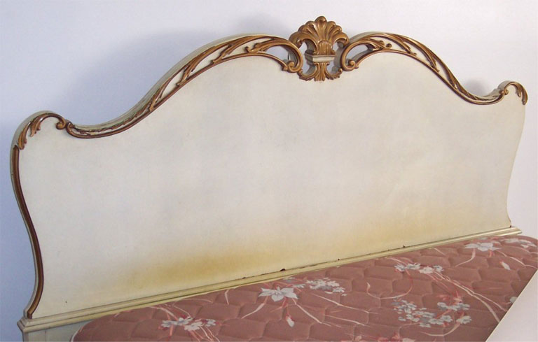 Headboard painted white with gold details.