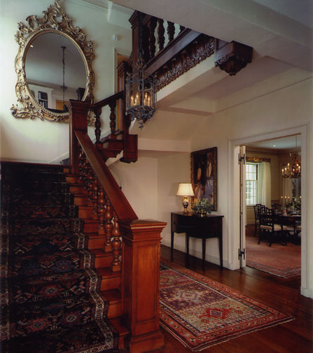 This staircase was originally painted. We stripped it, stained it in a warm pine color, added a shadow glaze and gold leaf highlights.